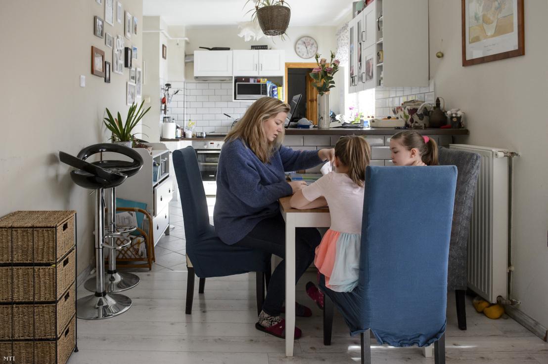 Egy édesanya segít lányainak az iskolai feladatok megoldásában