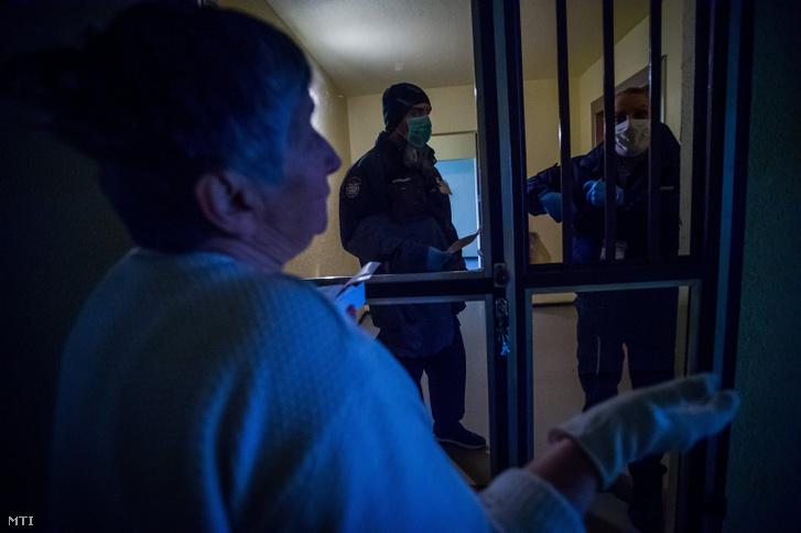 Védőmaszkot és gumikesztyűt viselő polgárőrök gyógyszereket szállítanak egy idős nőnek a XIII. kerületben 2020. március 23-án. Az Országos Polgárõr Szövetség közterületi és külterületi szolgálattal segíti a koronavírus-járvány miatt kialakult helyzet enyhítését. A polgárőrök legfőképpen élelmiszerek gyógyszerek beszerzésével és kiszállításával segítenek az időseknek.