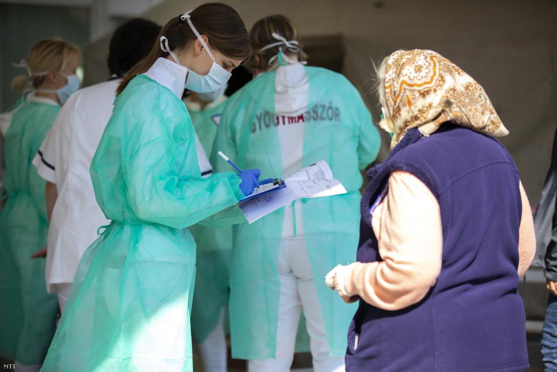 Vizsgálatra érkező nővel beszélget egy védőmaszkot viselő nővér Nagykanizsán a Kanizsai Dorottya Kórház előtt 2020. március 20-án. A koronavírus-járvány miatt az intézmény előtt szűrõsátrakat állítottak fel és bevezették az egykapus beléptetést.