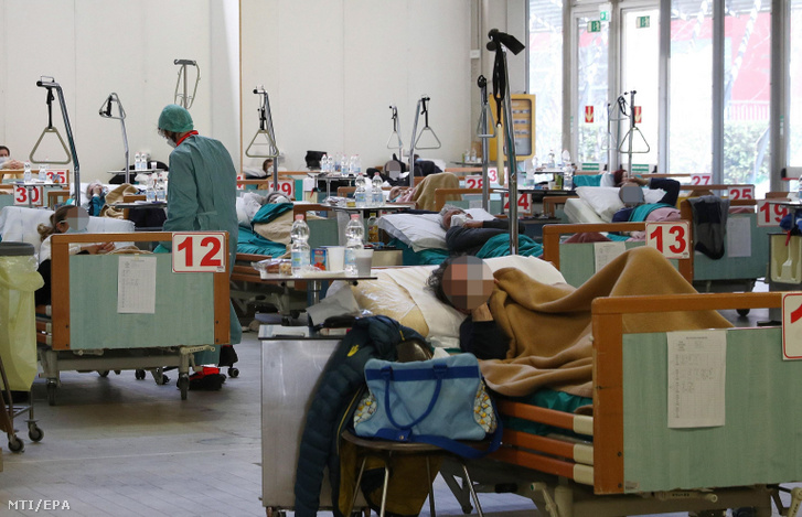 Védőmaszkot viselő egészségügyi dolgozó ellátja a betegeket a koronavírus-járvány miatt felállított ideiglenes kórházban az észak-olaszországi Bresciában 2020. március 24-én.