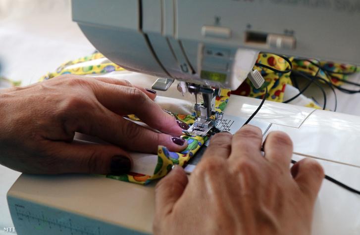 Kétrétegű textil védőmaszkokat varr egy önkormányzati dolgozó otthonában 2020. március 18-án.