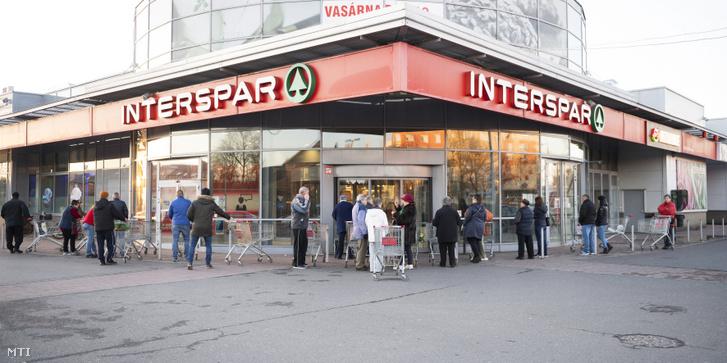 Vásárlók várakoznak már a nyitás előtt egy élelmiszerüzletnél Nyíregyházán 2020. március 14-én
