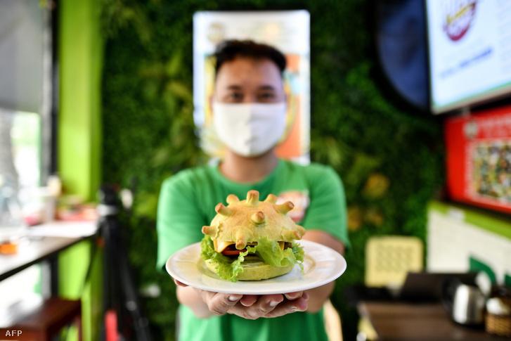 A Pizza Home nevű étterem tulajdonosa büszkén mutatja a koronavírus által ihletett hamburgert