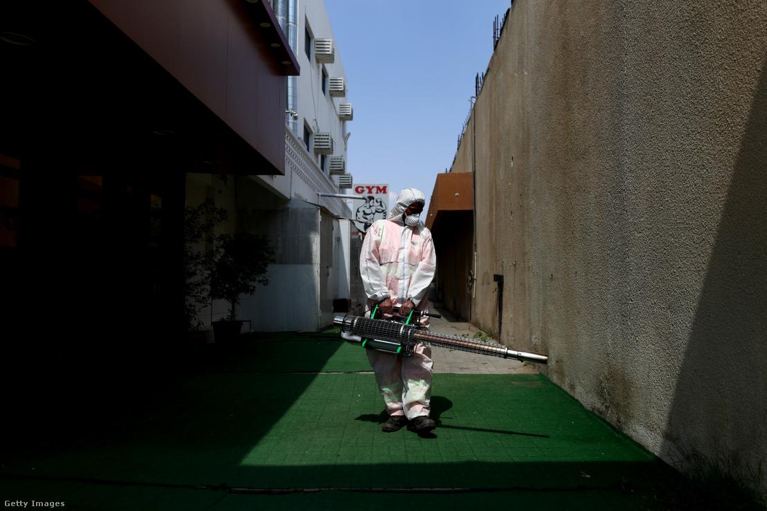 Az utcákat fertőtleníti egy munkás az Egyesült Arab Emirátusokbeli Sardzsa városában 2020. márcus 25-én.