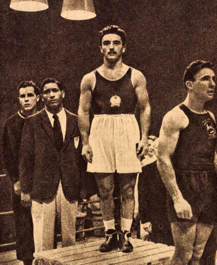 Papp László a győzelmi emelvényen Helsinkiben 1952-ben. Előtte a dél-afrikai Van Schalkwyk, a 2. helyezett, mögötte az argentin Herrera, a 4. és a szovjet B. Tyisin, a 3. helyezett. Forrás: Képes Sport 1956. 39. szám / Arcanum adatbázis