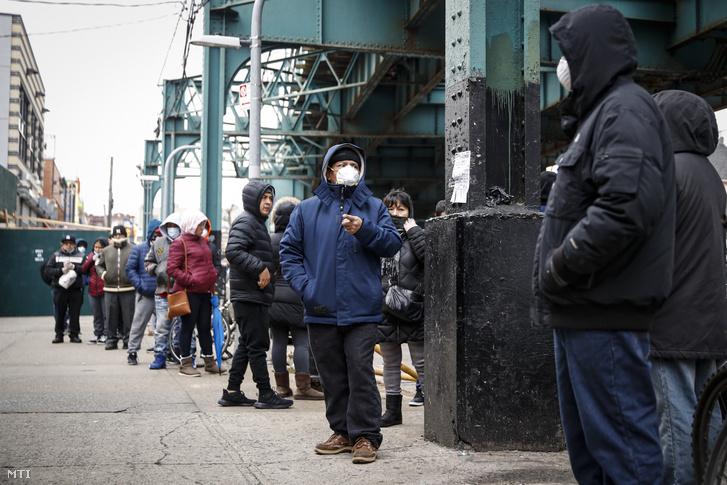 Védőmaszkos vásárlók várakoznak egy gyógyszertár előtt New York-ban 2020. március 25-én.