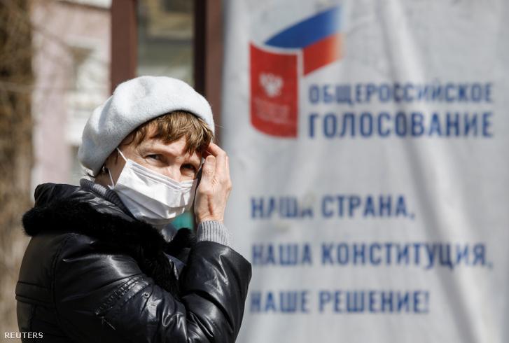 Nő arcmaszkban Sztavropolban, háttérben az alkotmánymódosításról szóló országos szavazás tájékoztatója 2020. március 26-án