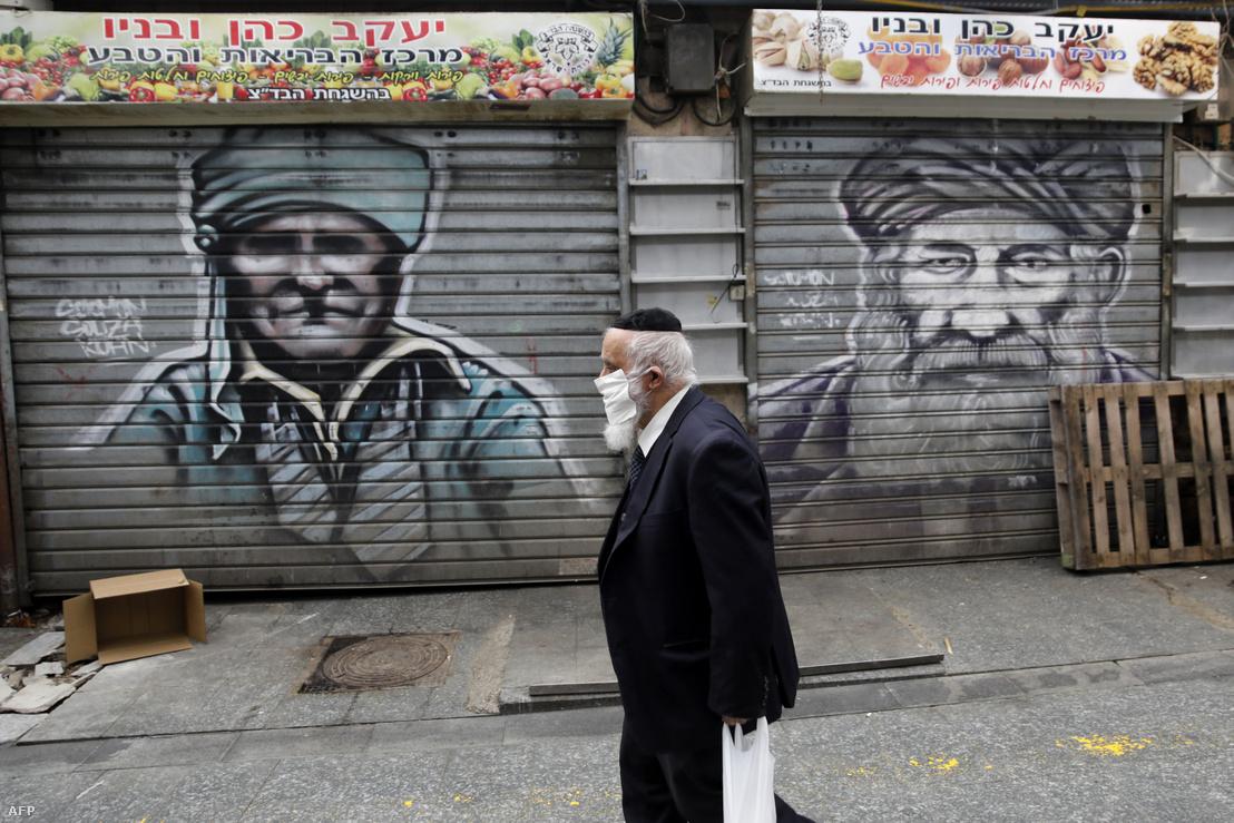 Arcmaszkos férfi sétál a koronavírus miatt részben bezárt jeruzsálemi Mahane Yehuda piacon 2020. március 26-án