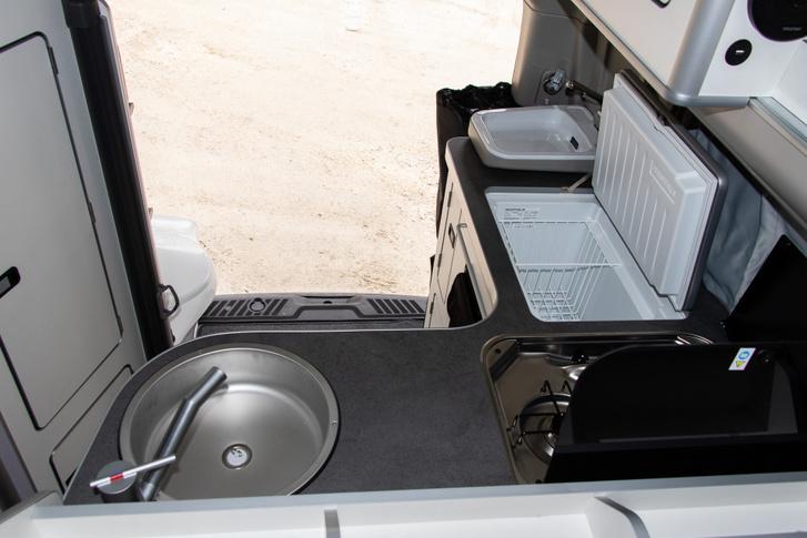 Van itt minden, balról jobbra: hideg/melegvizes mosogató, kétlapos gáztűzhely, 40 literes hűtőláda, mosdó és a végén a hátfalon a zuhany csatlakozója.