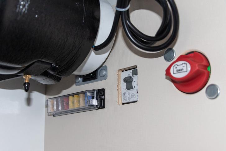 Egy sor 12 voltos biztosíték, egy 230 voltos Fi relé, és a nagy piros tekerős főkapcsoló. A bojler mögött a vízszivattyú kapcsolója rejtőzik.