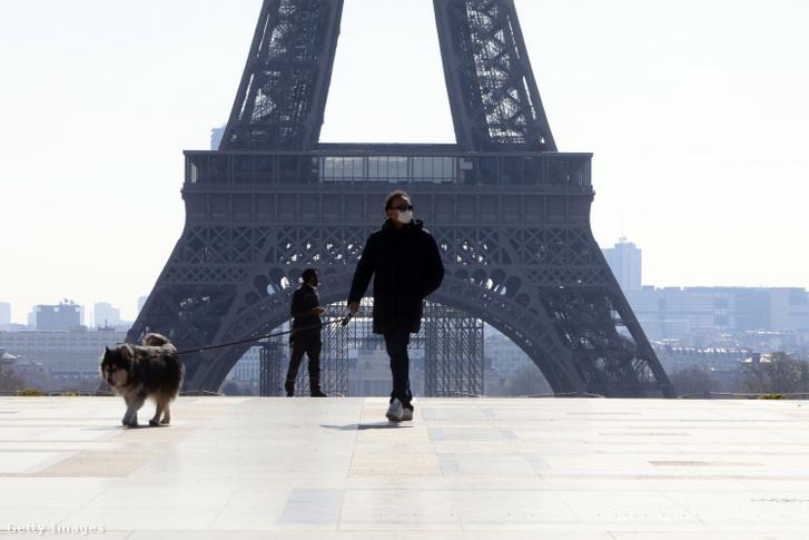 Maszkot viselő férfi és kutyája Párizsban 2020. március 26-án.