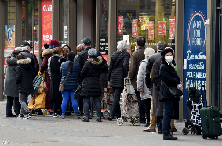 Vásárlók állnak sorban egy párizsi bolt előtt 2020. március 17-én.