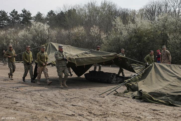 A Bukarest mellett épülő katonai járványkórház egyik sátrát rakják össze román katonák