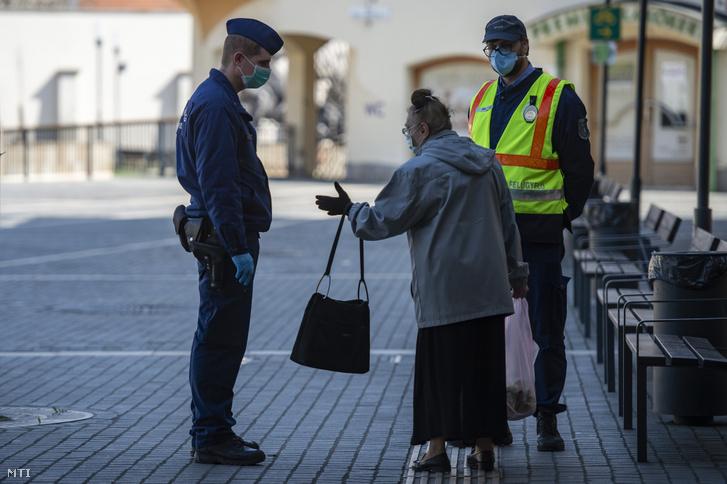 Idős járókelõvel beszélget egy rendőr az egri Zalár József utcában a kijárási korlátozás kezdetének napján 2020. március 28-án.