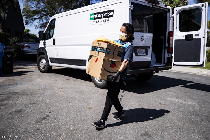Csomagot visz házhoz az Amazon internetes kereskedelmi cég egyik kiszállítója Los Angelesben 2020. március 26-én. Az Egyesült Államokban több mint hárommillió fölé emelkedett az első alkalommal munkanélküli segélyt kérők száma az elmúlt héten mert az új koronavírus által okozott járvány megfékezését célzó szigorú intézkedések hirtelen megállították a gazdaságot és elbocsátási hullámot indítottak el.