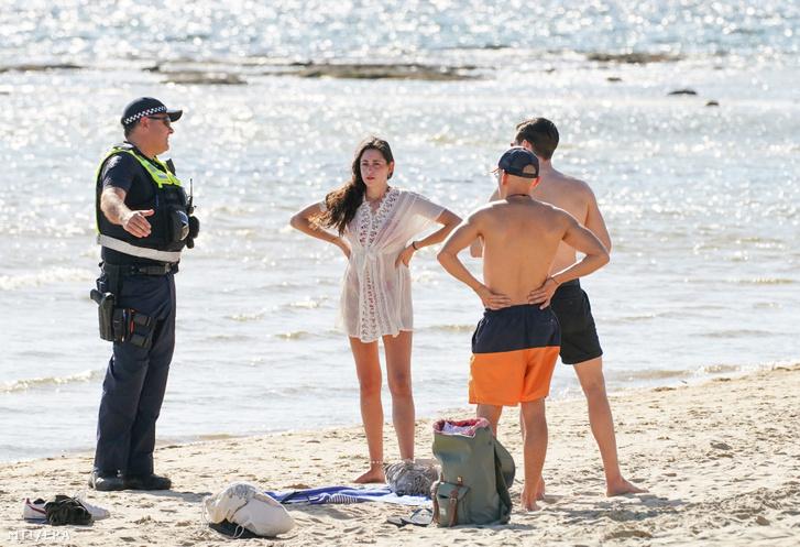 Rendőr tájékoztatja a látogatókat a Brighton Beach lezárásáról Melbourne-ben 2020. március 28-án.