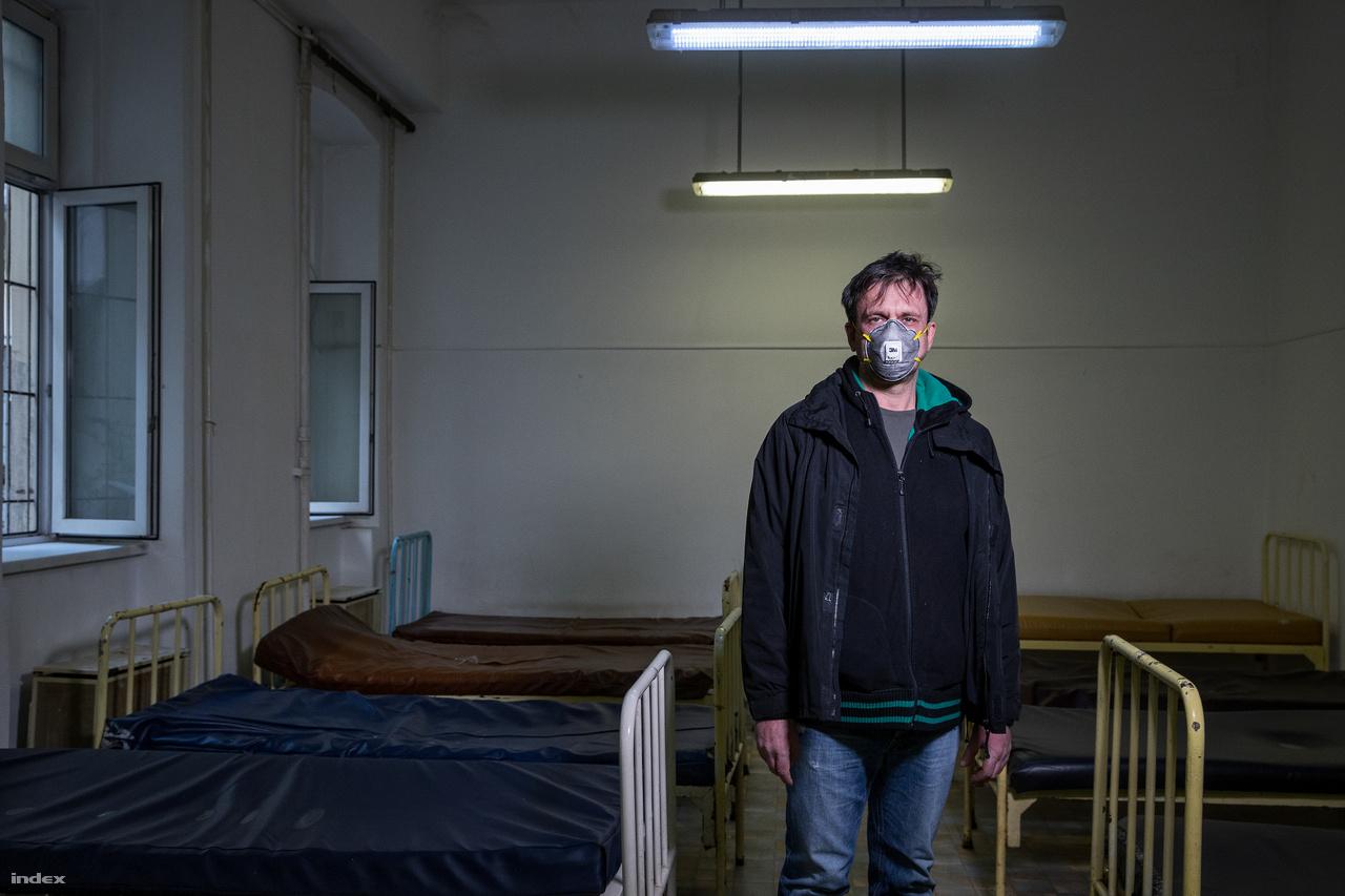 """Másfél hete már a szállón is kötelező a szájmaszk, belépés után mindenkinek kezet kell mosni, 50 helyett már csak 35 férőhelyet biztosítanak, hogy ezzel is csökkentsék a fertőzésveszélyt, és szombattól átálltak a 24 órás nyitva tartásra, amire """"nagyon készültek"""". A RÉS Podmaniczky utcai szállóján normális esetben este hattól reggel nyolcig húzhatják meg magukat a hajléktalan nők. Akijárási korlátozás bevezetésemiatt szombattól egész nap bent maradhatnak a szállón. Többségük ugyanis a veszélyeztetett korosztályba tartozik és """"iszonyú egészségügyi állapotban"""" van, mondja Buzás Endre, a RÉS projektvezetője.""""Mielőtt bevezettük az óvintézkedéseket, a lakógyűlésen kértem tőlük, hogy ne menjenek be a nappali melegedőkbe, ne bandázzanak kint, próbáljanak meg nem kukázni, ne csikkezzenek! A többsége egyébként betartja, kivéve a bandázást"""". Hozzáteszi, ők nem hatóság, senkit nem zárhatnak be.""""Próbáljuk benntartani őket úgy, hogy ne legyen feszkó"""", mondja. Legnagyobb félelmük, hogyan tudják majd kezelni a pszichiátriai betegeket és a függőket. """"Vettünk bort, cigit meg töményet, ha csak emiatt mennének ki, ne menjenek. Megbeszélem az addiktológussal, hogy kinek, mennyit lehet adni.""""Buzás azt mondja lassan két hete nem alszik. Miközben szervezi a szálló életét, a Menhely Alapítvány krízisautóján és diszpécserként is dolgozik. """"Ijesztő látni, hányan kerülnek ki az utcára. A munkahely elvesztése miatt családok pörögnek ki az albérletből. Ez durván megugrott az utóbbi időben. A családokkal egyáltalán nem tudunk mit kezdeni, mert a rendelet szerint felvételi stop és kijárási tilalom van. Egy ilyen helyzetben a legrosszabbat tudod válaszolni. Azt, hogy nem tudsz segíteni!"""" Jó pár kollégája sírta már el magát a tehetetlenségtől. """"Próbálom megnyugtatni őket. Elmagyarázni nekik, hogy meddig húzódik a felelősségük, mi az a pont, amikor azt kell mondani, hogy stop, ez már rajtuk és a szakmaiságon túlmutat."""""""