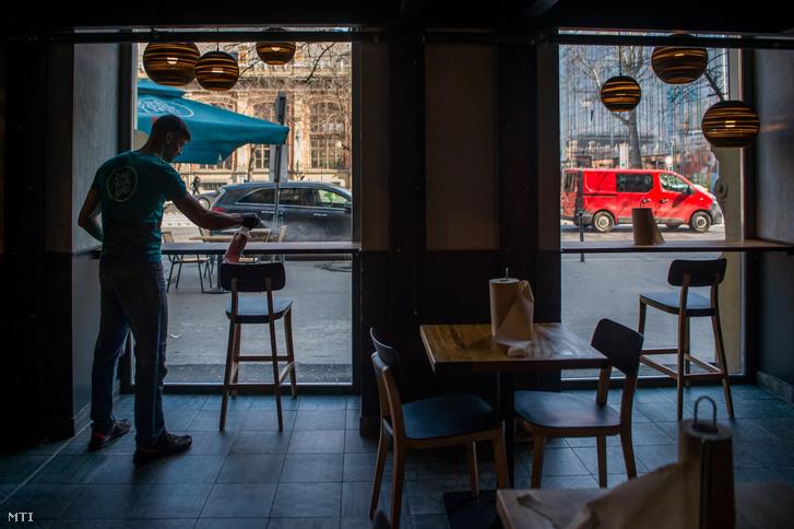 Budapesti gyorsétteremben fertőtlenít egy dolgozó nyitás előtt 2020. március 19-én. Március 28-tól kijárási korlátozást vezetett be a kormány, a vendéglátó üzemekben is tilos a tartózkodás, ezért azok az éttermek, ahol nincs kiszállítás, bezártak.