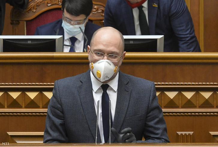 A koronavírus-járvány miatt védőmaszkot viselő Denisz Smihal ukrán miniszterelnök beszél a kijevi parlament rendkívüli ülésén Kijevben 2020. március 30-án