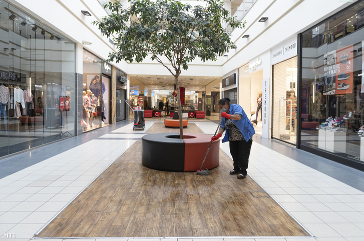 Védőmaszkot viselő takarító dolgozik a szinte teljesen elnéptelenedett nyíregyházi Nyír Plaza Bevásárlóközpontban