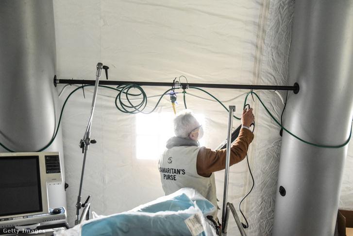 Egy férfi oxigéncsöveket szerel fel a New-yorki Central Parkban létesített szükségkórházban 2020 március 30-án.