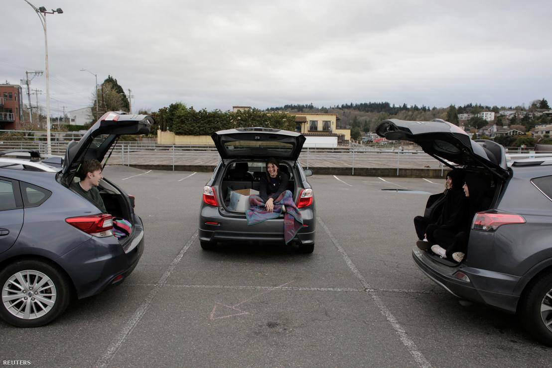 Tavolságot tartva autójuk csomagtartójából beszélgetve töltenek együtt időt egy baráti társaság tagjai egy seattle-i parkolóban 2020 március 27-én.