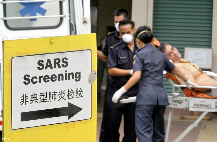 Mentősök emelnek ki a mentőkocsiból egy beteget akit az atípusos tüdőgyulladás azaz a súlyos akut légúti szindróma (SARS) tüneteivel szállítottak egy szingapúri kórházba 2003. szeptember 9-én