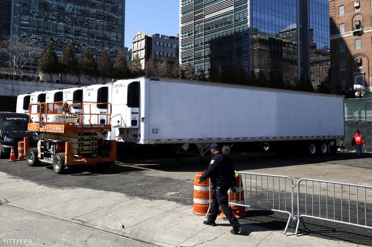 Hűtős teherautók sorakoznak a New York-i Bellevue kórház közelében 2020. március 26-án.