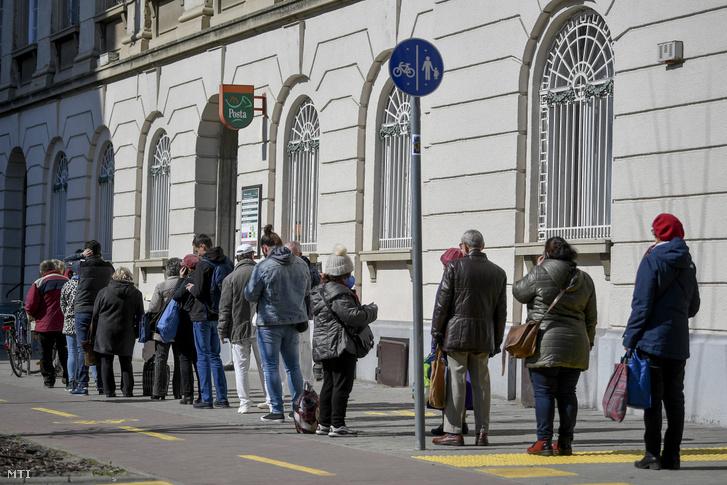 Sorban állók a Hatvan utcai posta előtt Debrecenben 2020. március 16-án. Csak annyi ügyfél tartózkodhat a postán, ahány ablak van.