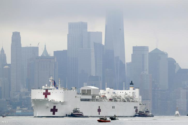 Az amerikai haditengerészet USNS Comfort kórházhajója Manhattan mellett halad el New York-i kikötője felé 2020. március 30-án. A tizenkét műtővel és ezer ággyal rendelkező hajó az érkezésétől számított 24 órán belül készen áll arra hogy az új koronavírussal megfertőződött betegeket kezelő kórházakat tehermentesítve más kórokkal küzdő pácienseket fogadjon.