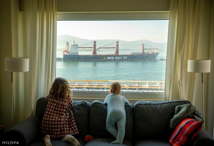 Teherszállító hajó elhaladását nézi két kislány nappalijuk ablakából az észak-spanyolországi Santander városban 2020. március 25-én a koronavírus-járvány terjedése miatt bevezett korlátozó intézkedések 11. napján.
