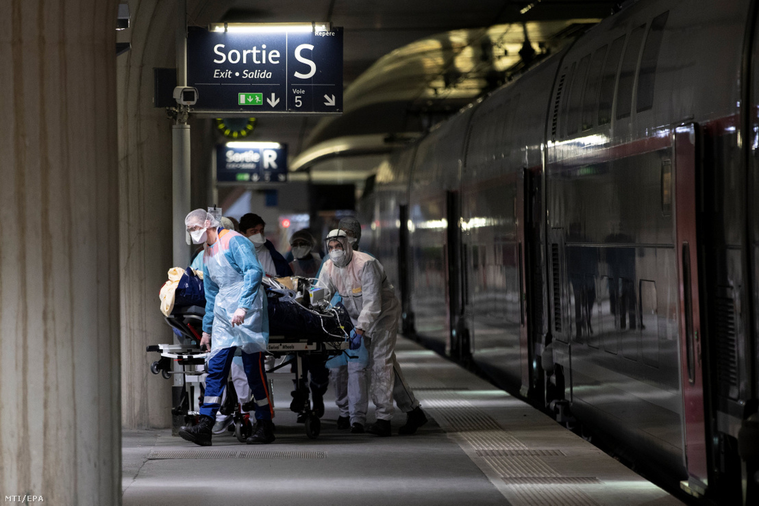 Az új koronavírussal fertőzött beteget visznek egy TGV szuperexpresszvonathoz a párizsi Austerlitz pályaudvaron 2020. április 1-jén. Két szerelvénnyel 36 beteget szállítanak el a fővárosból a nyugat-franciaországi Bretagne kórházaiba.