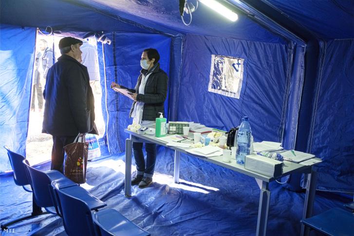 Az új koronavírus romániai gyors terjedése miatt asszisztens kérdez ki egy érkező beteget a Csíkszeredai Megyei Sürgősségi Kórház kapujában felállított elővizsgálati sátornál 2020. március 16-án.