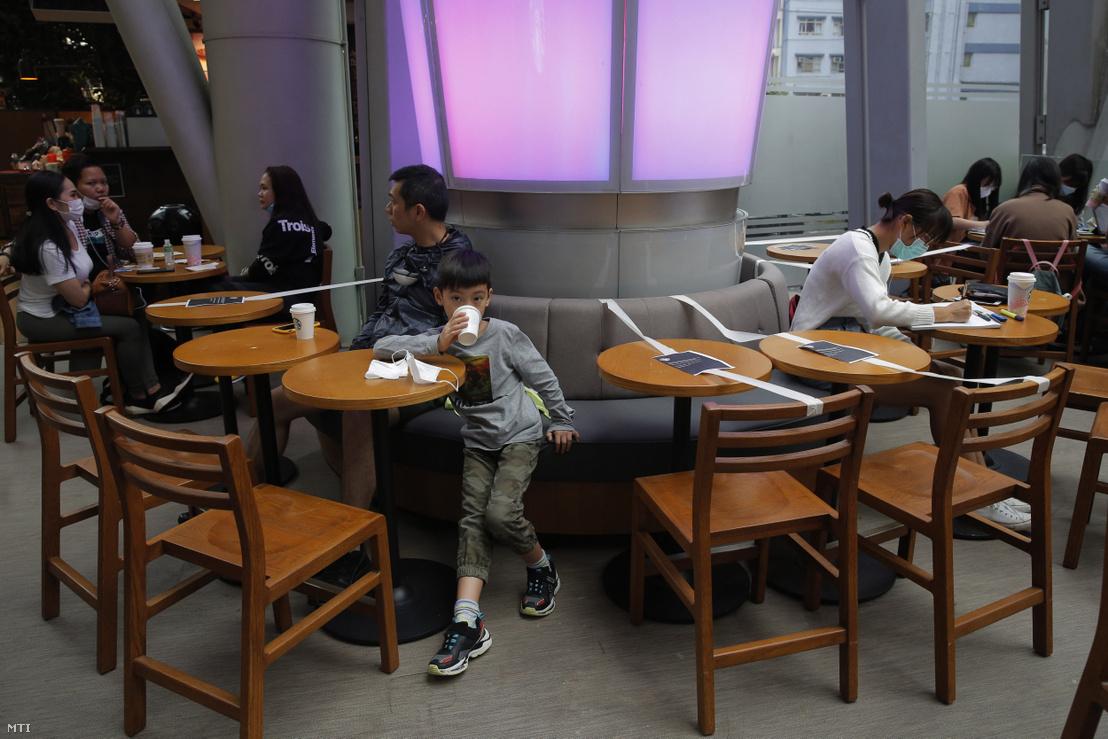 A vendégek közötti biztonságos távolságra figyelmeztető csíkok egy hongkongi kávézóban 2020. március 29-én.