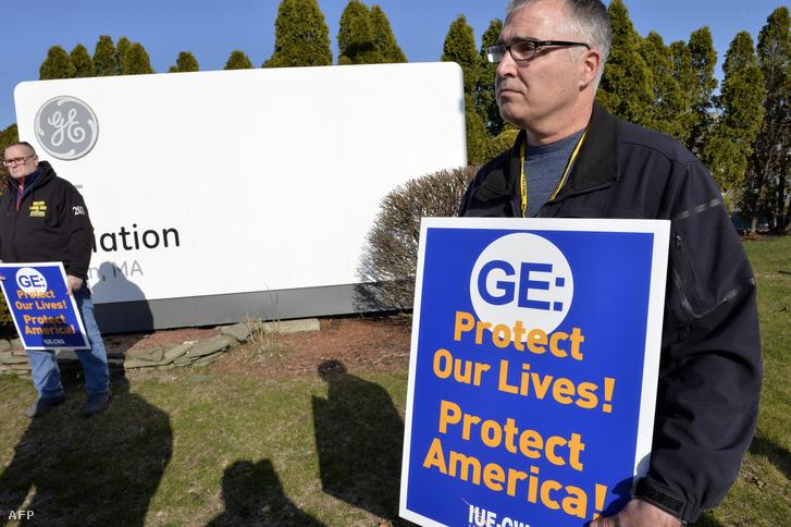 A General Electric dolgozói tüntetnek a GE Massachusettsi gyára előtt 2020. március 31-én, tisztább és biztonságosabb munkakörülményekért a járvány ideje alatt és azért, hogy a cég kirúgások helyett inkább több lélegeztetőgépet gyártson.