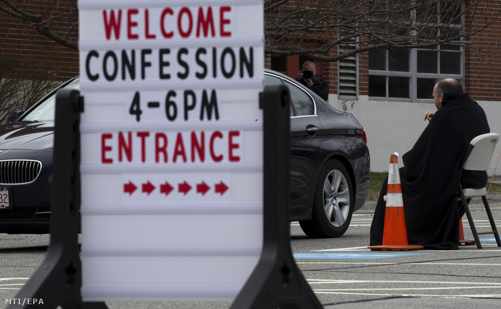 Corey Bassett-Tirrell katolikus pap az egyik autóban ülõ hívõ gyónását hallgatja a koronavírus-járvány miatt bezárt Szent Mária-templom parkolójában a Massachusetts állambeli Chelmsfordban 2020. április 1-jén. A hívõknek szerdánként 16 óra és 18 óra között biztosítanak lehetõséget a gyónásra.