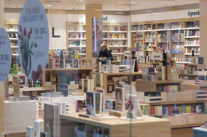 Vásárló egy könyvesboltban a szinte teljesen elnéptelenedett nyíregyházi Nyír Plaza Bevásárlóközpontban 2020. március 23-án.
