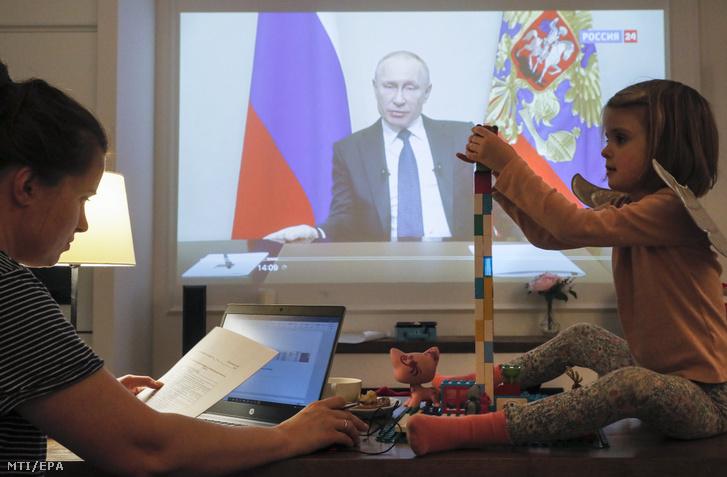 Orosz nő és lánya nézi Vlagyimir Putyin kormányzati intézkedésekről szóló beszédét.