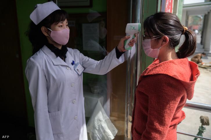 Egy érkező lázát mérik egy phenjani kórházban 2020 április 1-én.