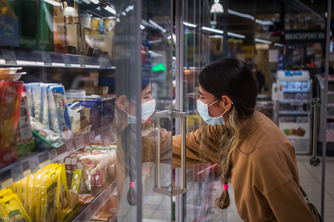Vásárló védőmaszkban egy fővárosi üzletben a kijárási korlátozás előtti napon 2020. március 27-én.