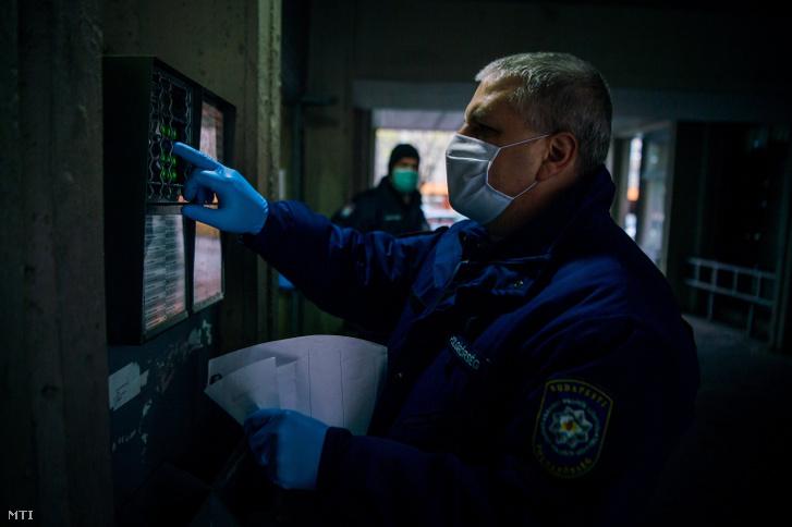 Védõmaszkot és gumikesztyût viselő polgárőrök gyógyszereket szállítanak ki idõseknek a XIII. kerületben 2020. március 23-án.