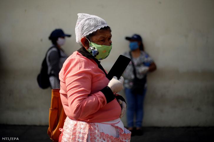A koronavírus-járvány miatt a salvadori kormány által élelmiszer-vásárlásra kiutalt 300 dollár értékű segélyért áll sorban egy asszony egy San Salvador-i bankfiók előtt 2020. április 1-jén.