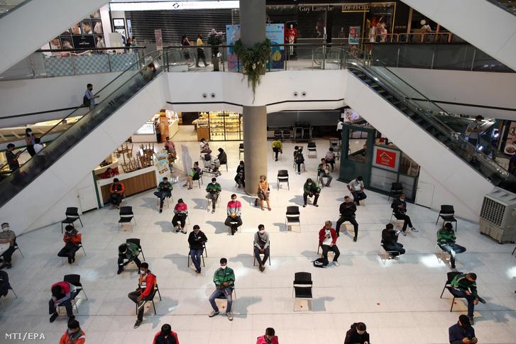 Ételfutárok várják a készülő ételeket egymástól biztonságos távolságra egy zárva tartó bangkoki bevásárlóközpontban 2020. március 24-én.