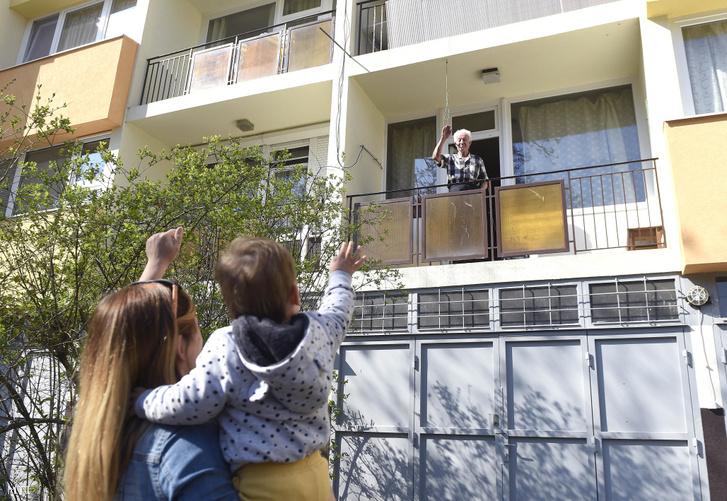 A háza előtt álló unokájának és dédunokájának integet egy 86 éves férfi szentendrei lakásának erkélyén 2020. március 20-án. A koronavírus-járvány miatt az idős ember nem hagyja el a lakását a helyi gondozási központ és családja látja el a szükséges dolgokkal.
