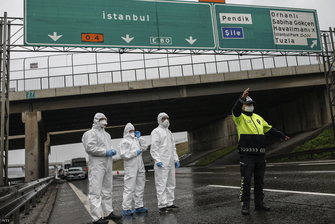 Egy buszt állít meg egy rendőrtiszt, hogy egészségügyi szakemberek megmérjék az utasok testhőmérsékletét Isztambulban 2020. március 29-én.
