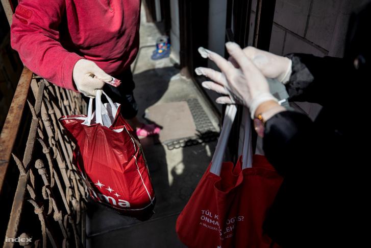 Önkormányzati dolgozó segít a bevásárlással a rászoruló időseknek Budapesten a koronavírus-járvány idején.