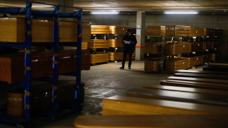 Arcmaszkos hatósági munkatárs ellenőrzi a koronavírus áldozatokat tartalmazó koporsókat a Collserola temetkezés parkolójában Barcelona közelében Montcada i Reixac-ban 2020. április 3-án