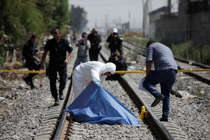 Törvényszéki technikus vizsgálja egy ismeretlen tettes által elkövetett gyilkosság áldozatának holttestét 2020. április 1-én Ecatepec közelében, Mexikóban.