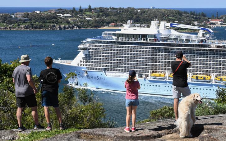 Turisták figyelnek egy óceánjárót Sydney kikötőjében