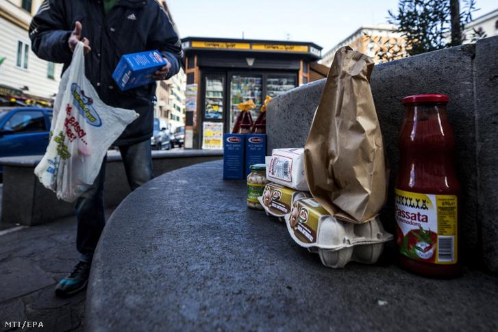 A nélkülözők számára egy padra kihelyezett élelmiszerek közül válogat egy férfi egy kis római téren a koronavírus-járvány idején 2020. április 2-án